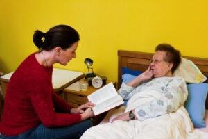 Caregiver Reading Book To Elder In Bed